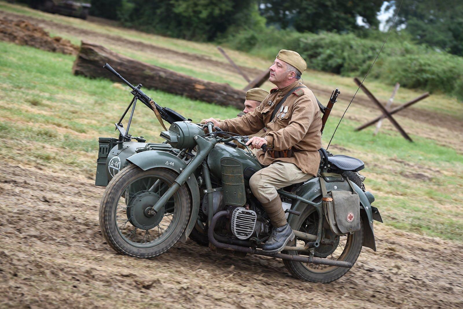 Re-enactors driving a motorbike at Capel Military Show